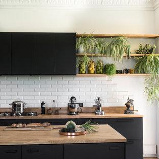 Exemple d'une grande cuisine parallèle éclectique avec des portes de placard noires, un plan de travail en bois, une crédence blanche, une crédence en carrelage métro, un îlot central, un sol marron, un plan de travail marron, un placard à porte plane et un sol en bois brun.