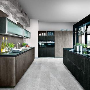 Cette image montre une très grande cuisine ouverte linéaire traditionnelle avec un îlot central, un placard à porte plane, des portes de placard en bois brun, une crédence marron, une crédence en bois, un électroménager noir et un sol gris.