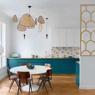 Réalisation d'une cuisine américaine nordique avec un évier 1 bac, un placard à porte plane, des portes de placard turquoises, une crédence multicolore et un sol en bois brun.