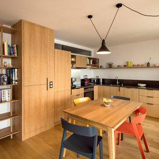 Cette photo montre une cuisine américaine tendance en L avec un évier encastré, un placard à porte plane, des portes de placard en bois brun, un électroménager encastrable, un sol en bois brun, aucun îlot, un sol marron et un plan de travail noir.