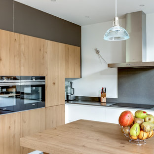 Exemple d'une cuisine américaine tendance en L de taille moyenne avec un placard à porte plane, des portes de placard en bois clair, une crédence blanche et aucun îlot.
