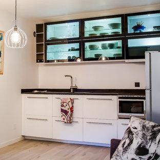 Réalisation d'une petite cuisine ouverte linéaire design avec un évier posé, des portes de placard blanches, une crédence noire, un électroménager encastrable, un sol en bois clair et aucun îlot.