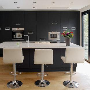Réalisation d'une cuisine américaine parallèle design de taille moyenne avec un évier encastré, un placard à porte plane, des portes de placard noires, un électroménager en acier inoxydable, un sol en bois clair, un îlot central, un plan de travail en quartz et un sol beige.
