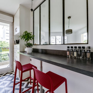 Design ideas for a mid-sized contemporary single-wall open plan kitchen in Paris with a single-bowl sink, beaded inset cabinets, white cabinets, stainless steel benchtops, white splashback, matchstick tile splashback, stainless steel appliances, cement tiles, with island and multi-coloured floor.