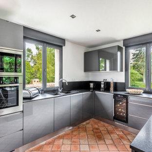 Cette photo montre une cuisine tendance en L avec un évier 2 bacs, un placard à porte plane, des portes de placard grises, une crédence noire, un électroménager en acier inoxydable, un sol en carreau de terre cuite, un îlot central, un sol orange et un plan de travail noir.