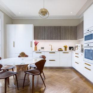 Idées déco pour une cuisine américaine contemporaine en L avec un placard à porte plane, des portes de placard blanches, une crédence blanche, un électroménager encastrable, un sol en bois brun et un plan de travail blanc.