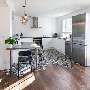Immagine di una cucina contemporanea con lavello integrato, ante bianche, top in quarzo composito, paraspruzzi bianco, pavimento nero, ante lisce, elettrodomestici in acciaio inossidabile, penisola e top nero