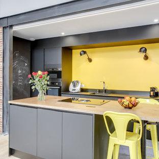 Réalisation d'une cuisine ouverte parallèle urbaine avec un évier encastré, un placard à porte plane, des portes de placard grises, un îlot central, un sol gris et un plan de travail gris.