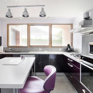 Exemple d'une cuisine américaine tendance en L de taille moyenne avec un évier 2 bacs, un placard à porte plane, une crédence grise et un îlot central.