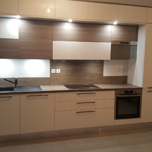 Photo of a large contemporary single-wall open plan kitchen in Marseille with a single-bowl sink, beaded inset cabinets, stainless steel cabinets, wood benchtops, white splashback, stainless steel appliances, cement tiles, with island, grey floor and beige benchtop.
