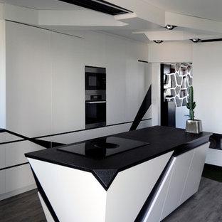 Cette image montre une grande cuisine ouverte linéaire design avec un placard à porte plane, des portes de placard blanches et un îlot central.