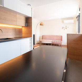 Idées déco pour une cuisine ouverte linéaire contemporaine de taille moyenne avec un placard à porte plane, des portes de placard blanches, une crédence en bois, aucun îlot, un évier intégré, un plan de travail en stratifié, un électroménager encastrable, un sol en linoléum, un sol multicolore et un plan de travail gris.
