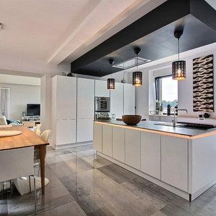 Idées déco pour une cuisine américaine parallèle contemporaine avec un évier posé, un placard à porte plane, des portes de placard blanches, une crédence blanche, un électroménager noir, un îlot central, un sol gris et un plan de travail noir.