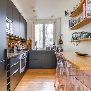 Cette photo montre une cuisine américaine tendance en L avec un évier intégré, un placard à porte plane, des portes de placard noires, un électroménager en acier inoxydable, un sol en bois brun, aucun îlot, un sol beige et un plan de travail noir.