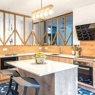 Inspiration for a contemporary l-shaped kitchen in Other with a submerged sink, flat-panel cabinets, light wood cabinets, beige splashback, wood splashback, black appliances, an island, blue floors and white worktops.