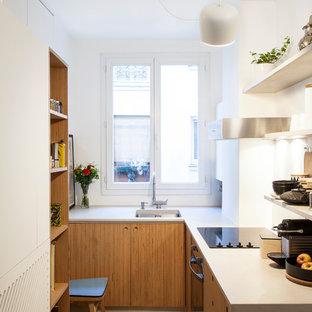 Idée de décoration pour une petite cuisine design en L fermée avec un placard à porte plane, des portes de placard en bois brun, un électroménager noir, aucun îlot, un évier encastré et une crédence blanche.