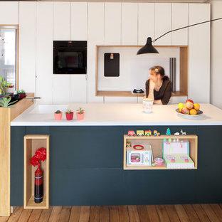 На фото: параллельная кухня-гостиная среднего размера в современном стиле с плоскими фасадами, белыми фасадами, паркетным полом среднего тона, островом и белым фартуком с