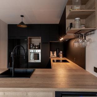 Cette photo montre une cuisine tendance en U de taille moyenne avec un évier posé, un placard à porte plane, des portes de placard noires, un plan de travail en bois, une crédence noire, une crédence en carreau de porcelaine, un électroménager noir et un plan de travail beige.