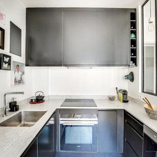 Exemple d'une petit cuisine tendance en U avec un plan de travail en quartz, un électroménager encastrable, un évier encastré, un placard à porte plane, des portes de placard noires et aucun îlot.