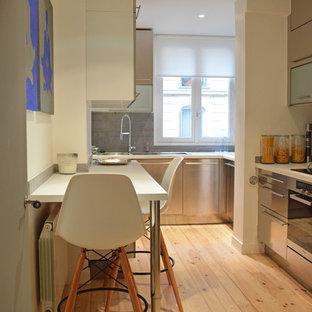 Aménagement d'une cuisine parallèle contemporaine fermée et de taille moyenne avec un évier encastré, un placard à porte plane, une façade en inox, une crédence grise, un électroménager en acier inoxydable, un sol en bois clair et aucun îlot.
