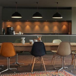 Exemple d'une grande cuisine américaine linéaire tendance avec un placard à porte plane, des portes de placard grises, une crédence grise, un électroménager encastrable, un sol en bois foncé et un îlot central.