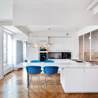 Idéer för ett stort modernt kök, med en undermonterad diskho, släta luckor, vita skåp, marmorbänkskiva, rostfria vitvaror, ljust trägolv och en halv köksö