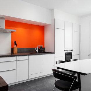 Cette image montre une grande cuisine américaine design en L avec des portes de placard blanches, un sol en carrelage de céramique, aucun îlot et une crédence orange.