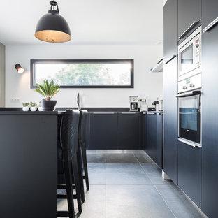 Idée de décoration pour une cuisine américaine design en L de taille moyenne avec un placard à porte plane, des portes de placard noires, un électroménager en acier inoxydable, un sol en ardoise et un îlot central.