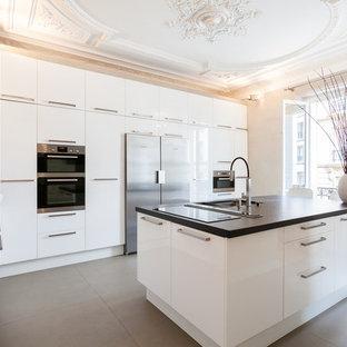 Cette image montre une grand cuisine parallèle design fermée avec un évier 2 bacs, un placard à porte plane, des portes de placard blanches, un électroménager en acier inoxydable et un îlot central.