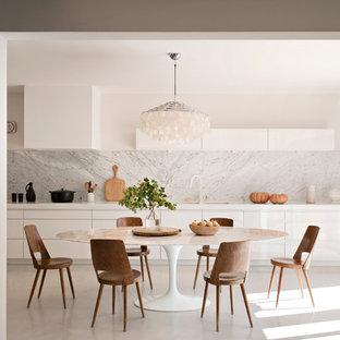 Aménagement d'une grande cuisine américaine linéaire contemporaine avec des portes de placard blanches et aucun îlot.