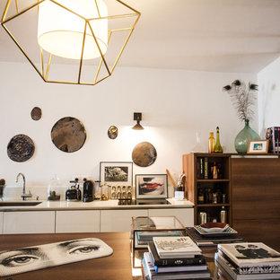 Idée de décoration pour une cuisine ouverte linéaire design de taille moyenne avec un évier 1 bac, des portes de placard blanches, une crédence blanche, un électroménager encastrable et un îlot central.