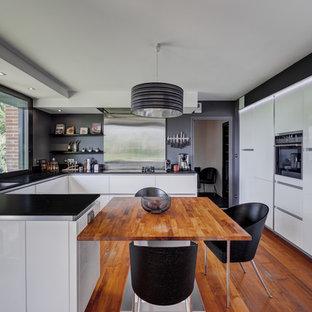 Aménagement d'une cuisine américaine contemporaine en U avec un évier encastré, un placard à porte plane, des portes de placard blanches, une crédence en fenêtre, un sol en bois brun, une péninsule et un plan de travail noir.