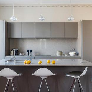 Inspiration pour une petite cuisine américaine parallèle design avec un évier encastré, un placard à porte plane, des portes de placard grises, une crédence grise, un sol en bois foncé, un îlot central et un plan de travail en inox.
