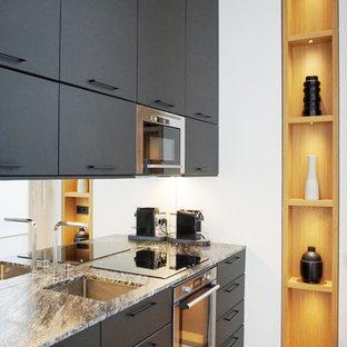 Inspiration pour une cuisine design avec un évier encastré, un placard à porte plane, des portes de placard noires, une crédence en carreau de miroir, un électroménager en acier inoxydable, un sol en bois clair, un sol beige et un plan de travail gris.