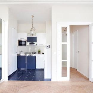 Modern inredning av ett litet linjärt kök med öppen planlösning, med släta luckor, vita skåp och ljust trägolv