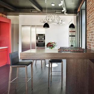 Idée de décoration pour une cuisine américaine linéaire design de taille moyenne avec un placard à porte plane, des portes de placard rouges, un électroménager en acier inoxydable, un sol en bois foncé et une péninsule.