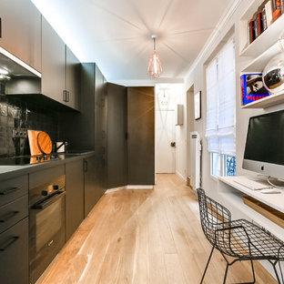 Cette photo montre une cuisine ouverte linéaire tendance de taille moyenne avec un placard à porte plane, des portes de placard noires, une crédence noire, une crédence en carreau de céramique, un électroménager noir, un sol en bois clair et aucun îlot.