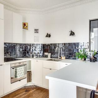 Idée de décoration pour une cuisine américaine design en U avec un évier posé, un placard à porte plane, des portes de placard blanches, une crédence bleue, un électroménager en acier inoxydable, un sol en bois brun et une péninsule.