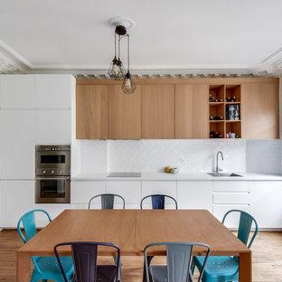 Cette image montre une cuisine américaine linéaire design avec un évier 1 bac, un placard à porte plane, des portes de placard en bois clair, une crédence blanche, un électroménager en acier inoxydable, un sol en bois clair et aucun îlot.