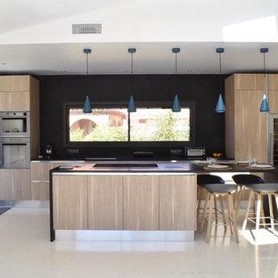 Cette image montre une grande cuisine design avec un placard à porte plane, des portes de placard en bois clair, une crédence noire, un électroménager en acier inoxydable et un îlot central.