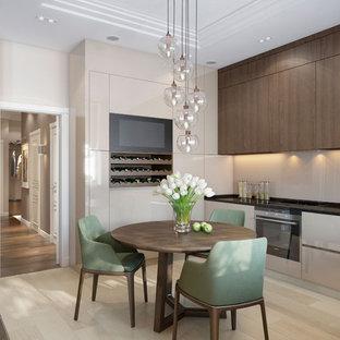 Moderne Wohnküche mit flächenbündigen Schrankfronten, beigen Schränken, Küchenrückwand in Beige, schwarzen Elektrogeräten, hellem Holzboden, beigem Boden und schwarzer Arbeitsplatte