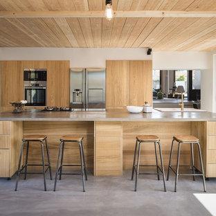 Idée de décoration pour une cuisine américaine parallèle design avec un évier 2 bacs, un placard à porte plane, des portes de placard en bois brun, un électroménager en acier inoxydable, béton au sol, un îlot central, un sol gris et un plan de travail gris.