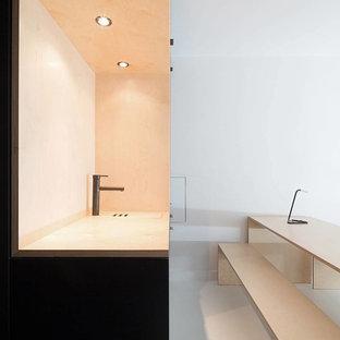 パリの小さいコンテンポラリースタイルのおしゃれなキッチン (アンダーカウンターシンク、フラットパネル扉のキャビネット、黒いキャビネット、木材カウンター、ベージュキッチンパネル、木材のキッチンパネル、パネルと同色の調理設備、クッションフロア、アイランドなし、白い床、ベージュのキッチンカウンター) の写真