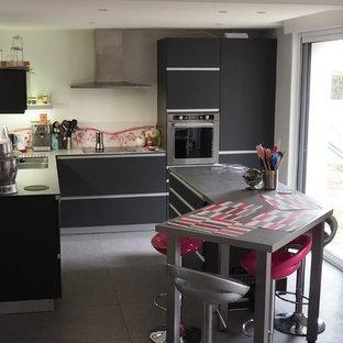Offene, Kleine Moderne Küche in L-Form mit Doppelwaschbecken, flächenbündigen Schrankfronten, grauen Schränken, Edelstahl-Arbeitsplatte, Küchenrückwand in Rosa, Glasrückwand, Küchengeräten aus Edelstahl, Keramikboden, Kücheninsel und grauem Boden in Nantes