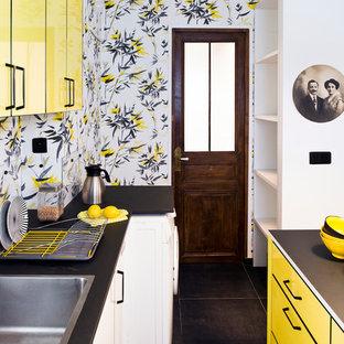 パリのエクレクティックスタイルのおしゃれなII型キッチン (ドロップインシンク、フラットパネル扉のキャビネット、黄色いキャビネット、黒い床、黒いキッチンカウンター) の写真