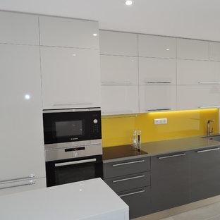 モンペリエの中サイズのモダンスタイルのおしゃれなキッチン (アンダーカウンターシンク、グレーのキャビネット、珪岩カウンター、黄色いキッチンパネル、ガラス板のキッチンパネル、パネルと同色の調理設備、セラミックタイルの床、アイランドなし) の写真