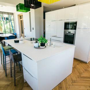 Idées déco pour une cuisine ouverte parallèle contemporaine avec un évier intégré, un sol en bois clair et un îlot central.