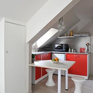 Inspiration pour une petit cuisine américaine design en L avec un placard à porte plane, des portes de placard rouges, un sol en bois clair et une péninsule.