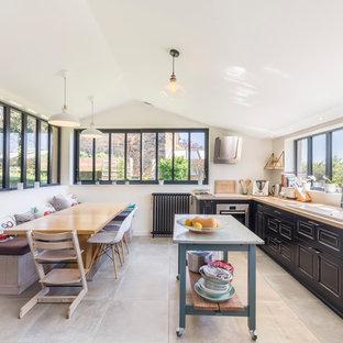 Cette photo montre une cuisine américaine chic en L avec un évier posé, un placard avec porte à panneau surélevé, des portes de placard noires, un plan de travail en bois, un électroménager en acier inoxydable, un sol en carreaux de ciment, un îlot central et un sol gris.