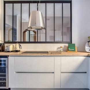 ニースの広いモダンスタイルのおしゃれなキッチン (フラットパネル扉のキャビネット、白いキャビネット、アイランドなし、ベージュのキッチンカウンター、シングルシンク、ラミネートカウンター、セラミックタイルの床) の写真